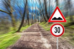 Hastighetsbegränsning 30 och hastighetsbula på skogvägen i rörelsesuddighet på en sol Royaltyfri Bild