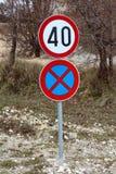 hastighetsbegränsning 40 och ingen parkering eller att stoppa undertecknar med vinterträd i bakgrund Royaltyfria Foton
