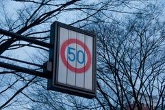 Hastighetsbegränsning på trafiktecknet för 50 kmph med torkade trädfilialer Royaltyfri Foto