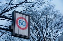 Hastighetsbegränsning på trafiktecknet för 50 kmph med torkade trädfilialer Arkivfoto