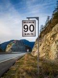Hastighetsbegränsningtecken med en uppehälle som är höger för att underteckna in bakgrunden bredvid en berghuvudväg arkivbilder