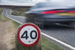 Hastighetsbegränsningtecken på den lantliga vägen med bilen Royaltyfri Fotografi