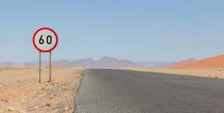 Hastighetsbegränsningtecken på en ökenväg i Namibia Arkivfoton