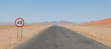 Hastighetsbegränsningtecken på en ökenväg i Namibia Royaltyfria Foton
