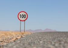 Hastighetsbegränsningtecken på en ökenväg i Namibia Royaltyfria Bilder