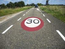Hastighetsbegränsningtecken på vägen Arkivbild