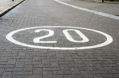 Hastighetsbegränsningtecken som målas på en lappad stads- väg Royaltyfri Foto