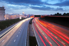 Hastighetstrafik på den dramatiska solnedgången Tid - ljus skuggar på motorwa Arkivbild