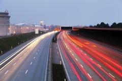 Hastighetstrafik på den dramatiska solnedgången Tid - ljus skuggar på motorwa fotografering för bildbyråer