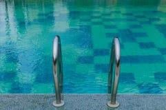 Hastigt greppstänger i den blåa simbassängen Royaltyfria Bilder