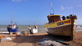 HASTINGS, GROSSBRITANNIEN - 15. JUNI 2013: Ein Strand startete Fischerboot mit starken Wellen im Hintergrund Lizenzfreie Stockbilder
