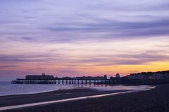 Hastings Pier. Silhouette of Hastings Pier in Sussex, UK. The sun has set and the twilight sky of orange and mauves is reflected in pools of seawater left by a stock image