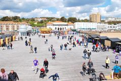 Hastings pier, England. People walk along the decking of the Victorian pier at Hastings in East Sussex, England on April 30, 2016. Closed since 2008 and badly Royalty Free Stock Images