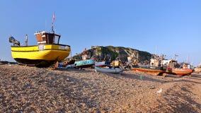HASTINGS, REINO UNIDO - 30 DE JULIO DE 2011: Barcos de pesca lanzados playa en la puesta del sol Foto de archivo libre de regalías