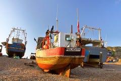 HASTINGS, REINO UNIDO - 30 DE JULIO DE 2011: Barcos de pesca lanzados playa en la puesta del sol Fotografía de archivo