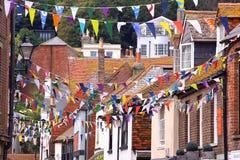 HASTINGS UK - JULI 31, 2011: En populär gata i Hastings den gamla staden med färgrika hus och flaggor Royaltyfri Bild
