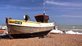 HASTINGS, UK - JUNE 15, 2013: A beach launched fishing boat with strong waves in the background Stock Image