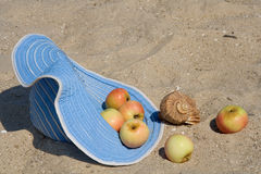 Hat, apples, shell on the sand Royalty Free Stock Photography
