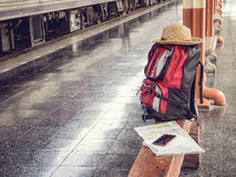 Hat, backpack, map, cellphone and notebook on bench at train station. Royalty Free Stock Images
