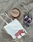 Hat with bag and flip-flops on the sand beach. royalty free stock photos