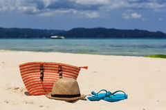 Hat, bag and flip flops on tropical beach Stock Photography