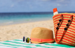 Hat, bag, sun glasses and flip flops on the beach. Traw hat, bag, sun glasses and flip flops on a tropical beach royalty free stock photo