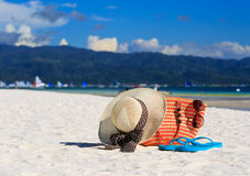 Hat, bag, sun glasses and flip flops on tropical beach Stock Images
