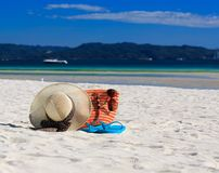 Hat, bag, sun glasses and flip flops on tropical beach Stock Photography