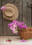 Hat and basket. Basket of flowers and a straw hat against the background of the old wooden walls Royalty Free Stock Photos