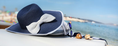 Hat on the beach with bag, sunglasses, shells and towel Royalty Free Stock Images
