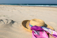 Hat on beach. Ladies straw hat with pink scarf on sunny sandy beach background Stock Photography