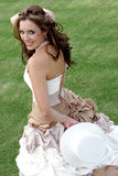 Hat Behind. A bride standing on grass holding a hat Royalty Free Stock Photography