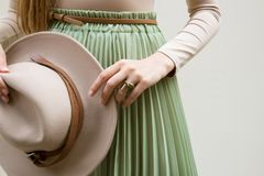 Hat, beige blouse and turqoise pleats skirt on light street backgraund. royalty free stock image