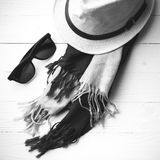 Hat and blue scarf with sunglasses black and white color. Hat and blue with sunglasses scarf on white table black and white color Stock Image