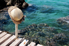 Hat with blue sea, rock and wood pier. In Thailand Stock Photography