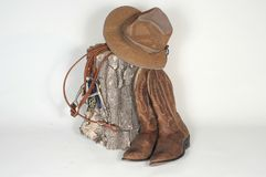 Hat, Boots and Reins w/stump. Hat, boots and reins resting on a old wooden stump on a white background Royalty Free Stock Photos