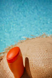 Hat and bottle of sun cream by the pool . Royalty Free Stock Image