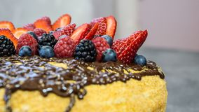 Hat cake, chocolate on top, juicy strawberries, raspberries and berries,side view stock photos