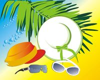 Hat, cap and glasses among the branches of palms Royalty Free Stock Photo