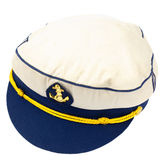 Hat of a captain at sea. White captain's hat with a blue brim, a braid trim and a patch with an golden anchor Stock Photos