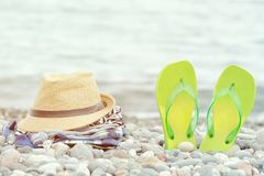 Hat, clothes and flip flops on the pebble beach. Sea in the back. Ground royalty free stock photo