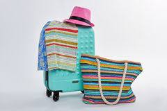 Hat, clothes on wheeled suitcase. Stock Images