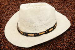 Hat and coffee beans. Panama hat on roasted beans in this South American coffee concept Royalty Free Stock Photography