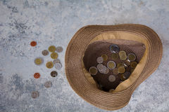 Hat and coins. A hat  placed on the ground with coins in it Stock Image