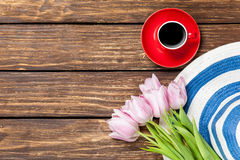 Hat and cup of coffee with tulips Stock Images