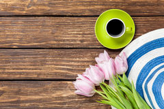 Hat and cup of coffee with tulips Royalty Free Stock Photography