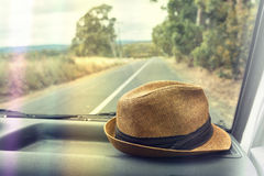 Hat on the dashboard of a car on a road trip Stock Photos