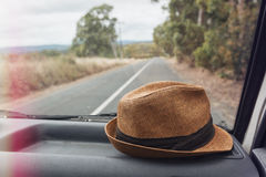 Hat on the dashboard of a car on a road trip Royalty Free Stock Photos