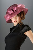 Hat and dress. A portrait of a vintage sexy lady wearing black dress and colored hat Stock Images