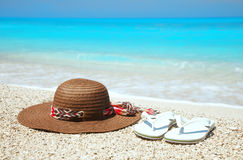Hat and flip-flops on a beach Stock Images